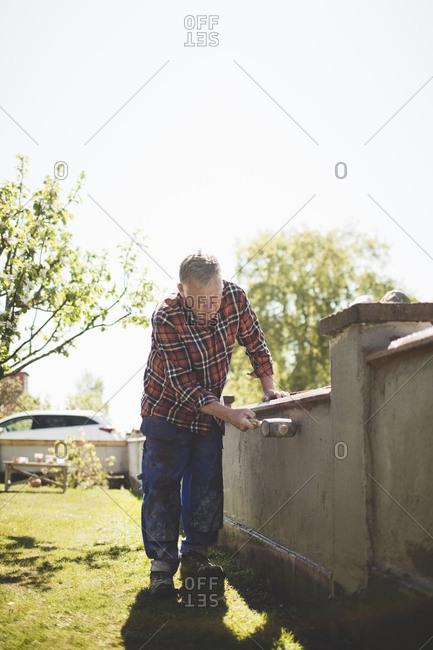 Full length of senior man examining concrete wall with hammer at yard against clear sky