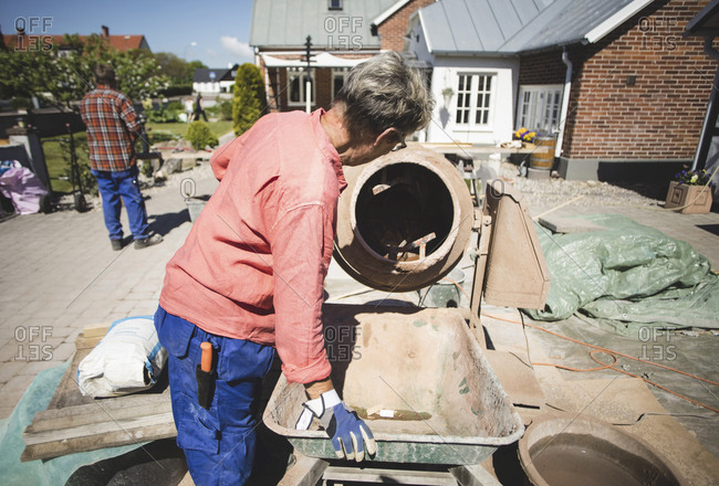 Side view of senior woman using cement mixer while man standing in background at yard
