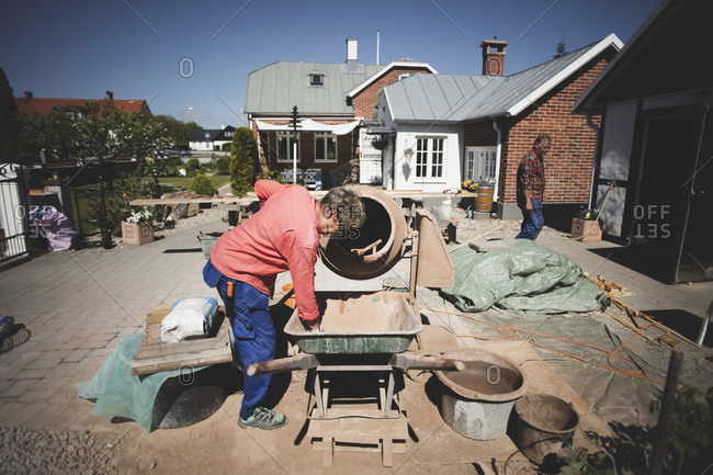 Senior woman using cement mixer at yard while man walking in background