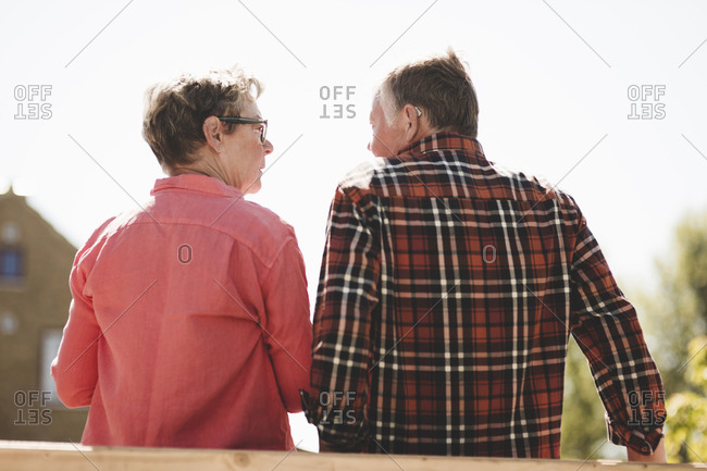 Rear view of senior couple looking at each other while standing against clear sky