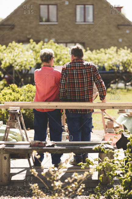 Rear view of senior couple standing by wooden plank at yard