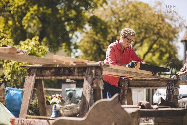 Senior woman cutting wooden plank with hand saw in yard
