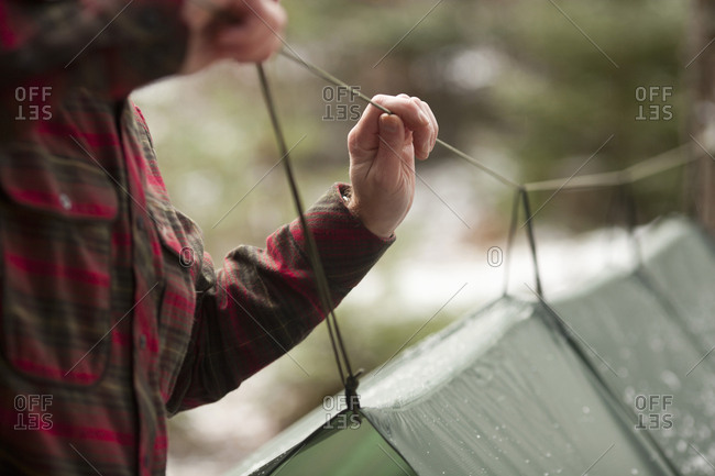 Midsection of man pulling rope of tent in forest