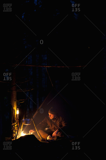 Man cooking food on campfire in forest at night