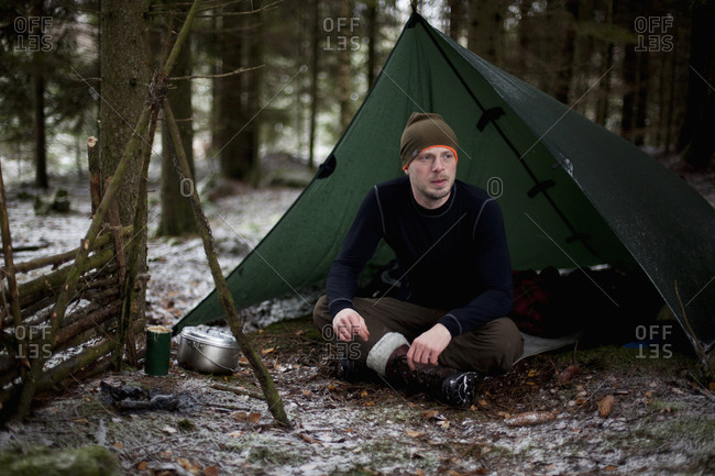 Thoughtful man sitting in tent at woodland during winter