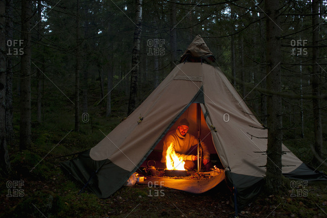 Mid adult man sitting by campfire in tent at woodland during night