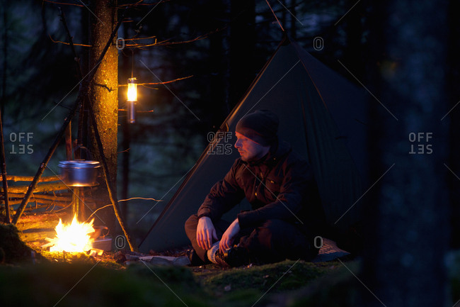 Man relaxing while cooking food on campfire in forest at night