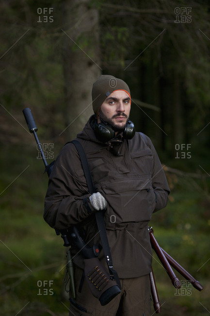 Portrait of confident male hunter standing in woodland