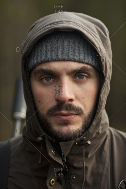 Close-up portrait of confident hunter in forest