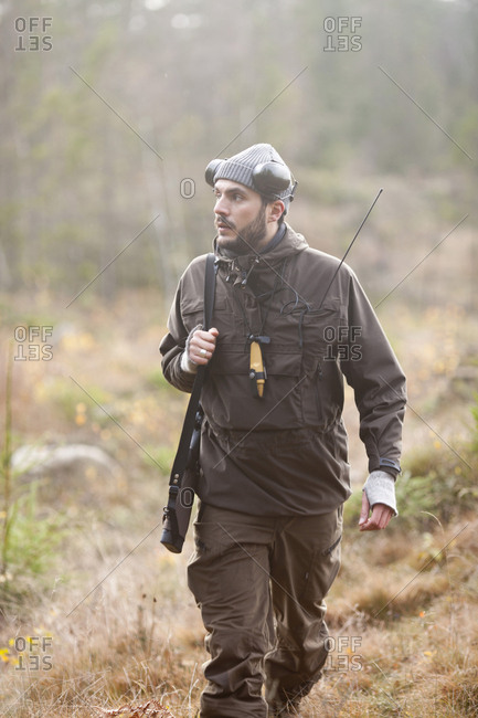 Thoughtful male hunter carrying rifle while walking in woodland