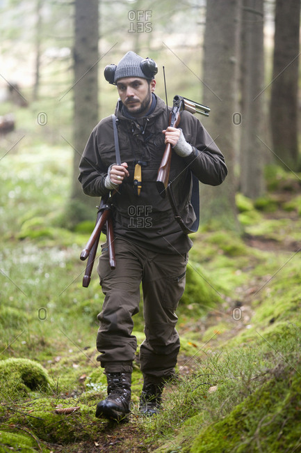 Full length of male hunter walking in woodland