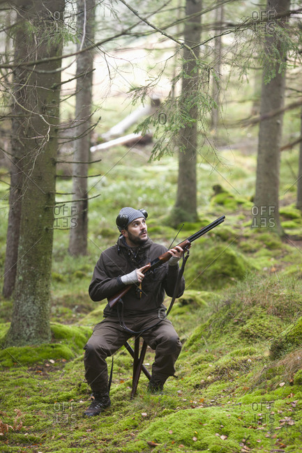 Mid adult hunter holding rifle while sitting on stool in forest
