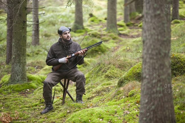 Mid adult male hunter holding rifle while sitting on stool in woodland