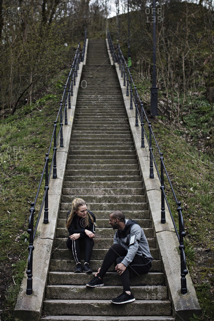 Multi-ethnic couple talking while sitting on steps after workout in forest