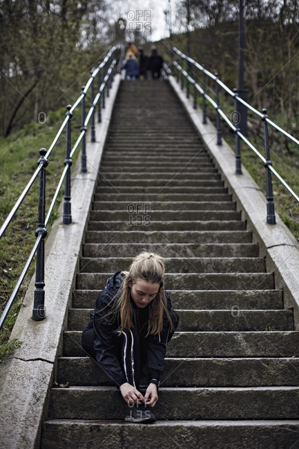Full length of young woman tying shoelace on steps