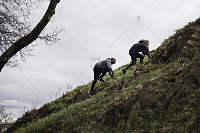 Low angle view of multi-ethnic couple climbing on hill in forest