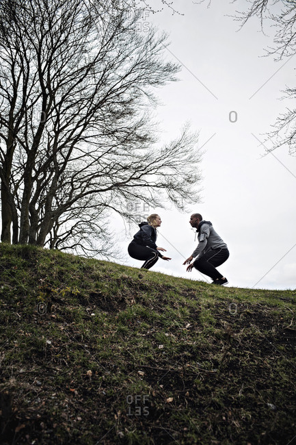 Low angle view of multi-ethnic couple jumping while crouching on hill