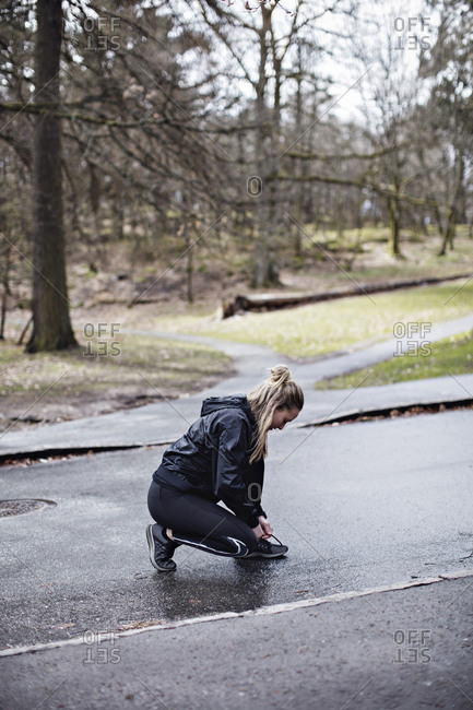 Full length side view of female athlete tying shoelace while crouching on road in forest