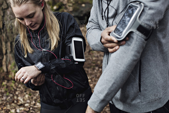 Male and female athletes wearing smart watch and arm band in forest