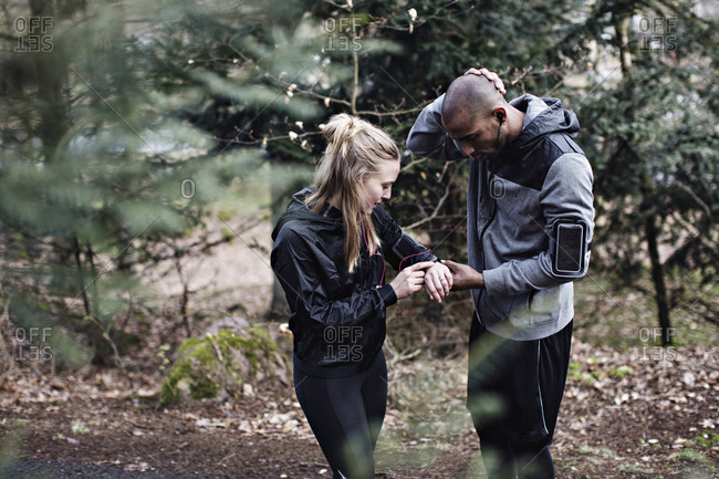 Male and female athletes checking smart watch in forest