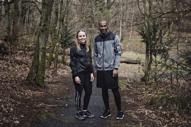 Full length portrait of confident male and female athletes standing in forest
