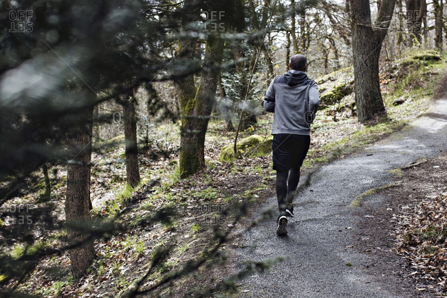 Full length rear view of male athlete jogging on narrow road in forest