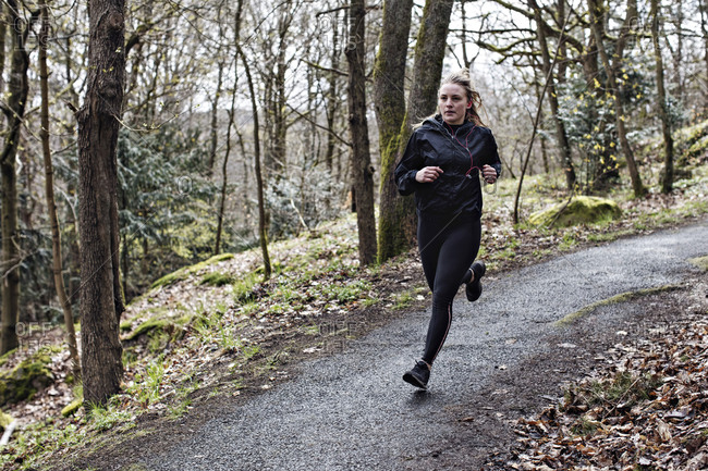 Full length determined female athlete running on narrow road in forest