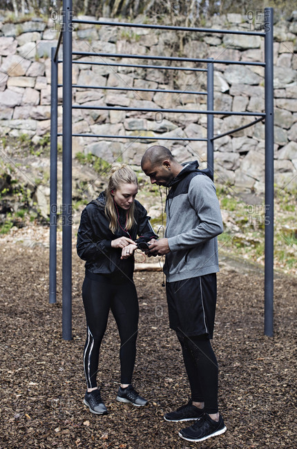Full length of male and female athletes using technologies by monkey bars in forest
