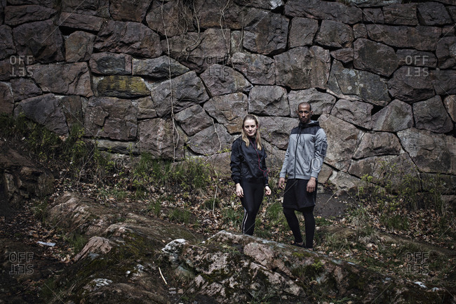 Portrait of confident male and female athletes standing against stone wall in forest