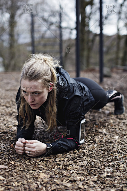 Determined female athlete performing plank position in forest