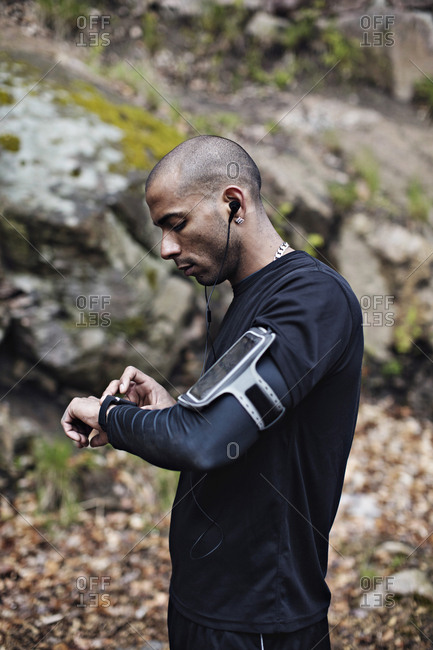 Side view of male athlete checking smart watch in forest