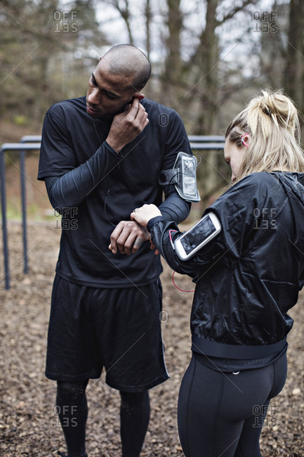 Male and female athletes wearing technologies in forest