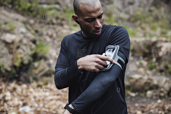 Male athlete using smart phone in arm band at forest