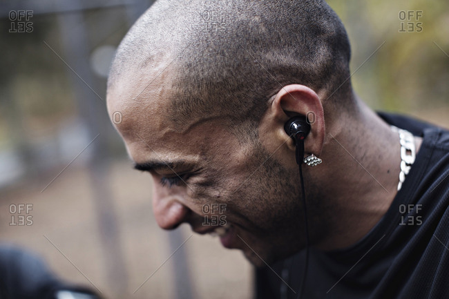 Side view of happy male athlete wearing in-ear headphones at forest