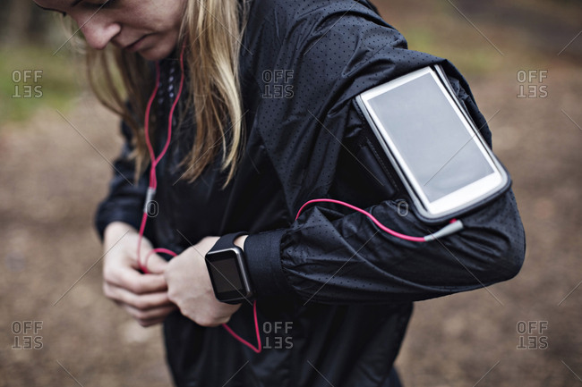 Midsection of female athlete with smart phone in arm band fixing headphones to jacket in forest