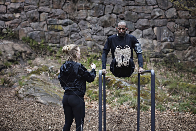 Rear view of female athlete looking at man exercising on parallel bars against stone wall in forest