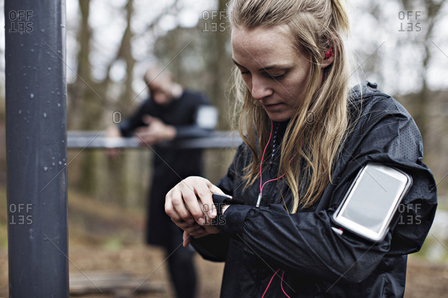Female athlete checking smart watch at forest while man standing in background