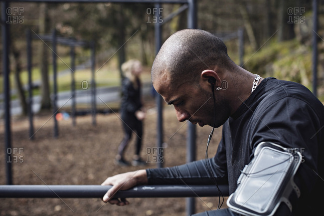 Side view of male athlete wearing headphones while exercising on parallel bars in forest