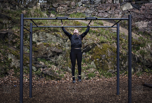 Full length of woman exercising on monkey bars at outdoor gym