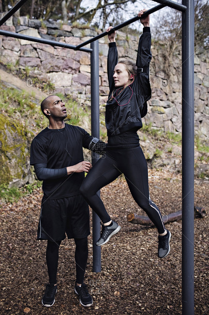 Mid adult man assisting woman exercising on monkey bars in forest