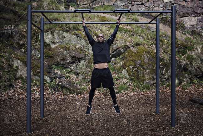 Full length of man exercising on monkey bars at outdoor gym