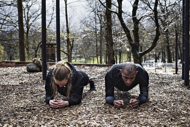 Multi-ethnic couple performing plank exercise at forest