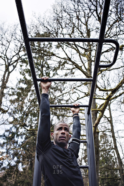 Low angle view of man exercising on monkey bars at outdoor gym