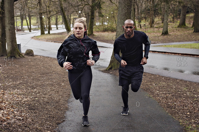 Full length of multi-ethnic couple jogging on wet street