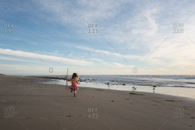 Girl running on beach holding stick