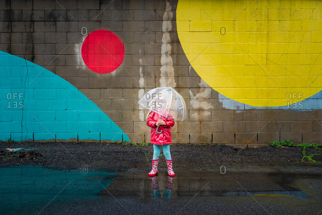 Girl with umbrella by painted wall