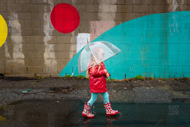 Girl with umbrella by a painted wall