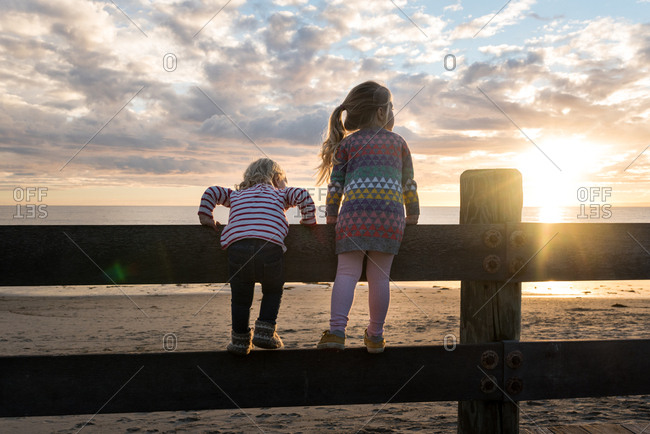 Girls on fence in coastal sunlight