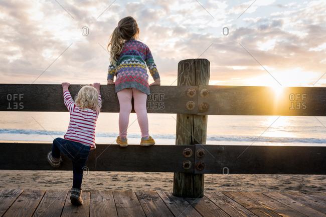Girls climbing fence in coastal sunlight
