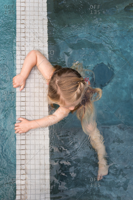 Girl holding wall in swimming pool